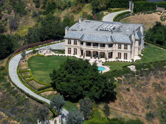 a-manicured-5-acre-lawn-huge-snake-like-driveway-and-a-ginormous-front-gate-surround-the-house