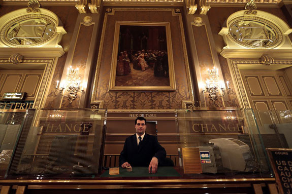 when-visitors-are-ready-to-cash-out-they-can-exchange-their-chips-with-assistant-cashier-gregory-francois-posing-here-in-the-salle-des-ameriques